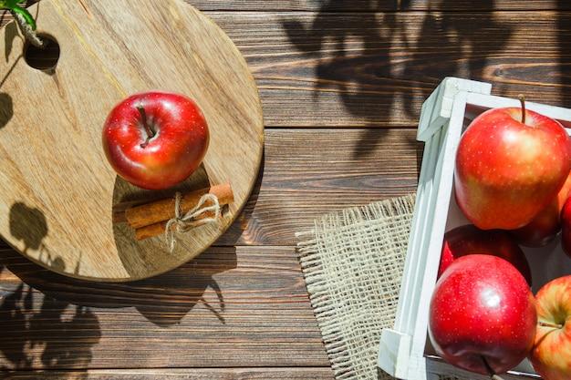 Appels in een witte doos en appel met kaneelstokjes op snijplank Gratis Foto