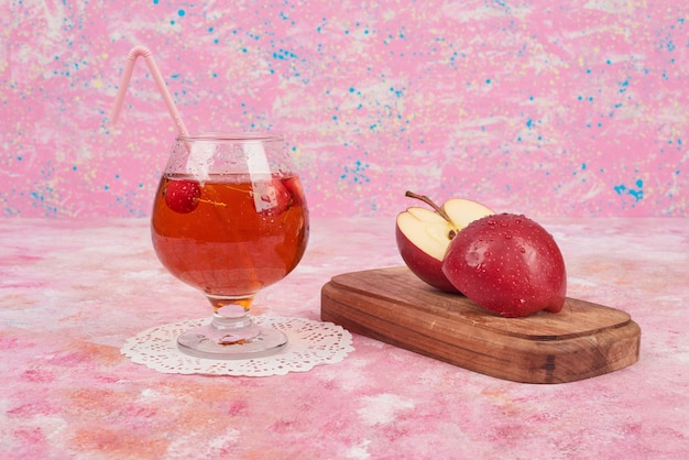 Appels op een houten bord met een glas sap rond. Gratis Foto