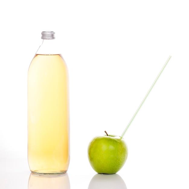 Appelsap in een glazen fles en groene appel met stro Gratis Foto