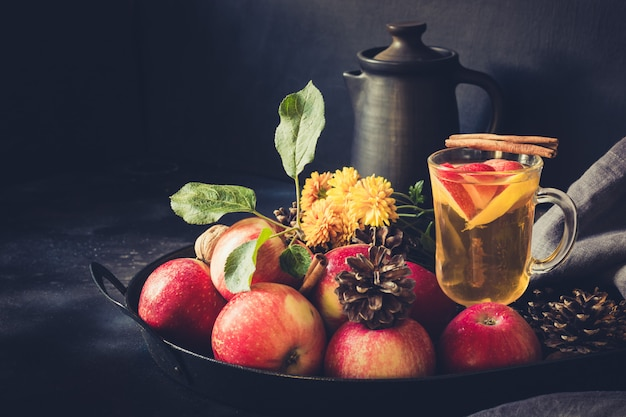 Appelthee met citroen, gekruid en kaneel in vintage dienblad op zwarte bord. herfst stilleven. detailopname. Premium Foto