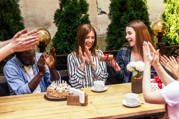 Applaus en verjaardagscadeaus geven van de beste vrienden op het feest op het terras van het café Gratis Foto