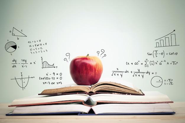 Apple op stapel open boeken met onderwijskrabbels en exemplaarruimte. onderwijs concept. Premium Foto