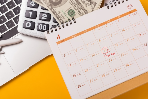 April van het jaar is belastingdag, close-upcalculator, laptopcomputer, kalender en dollargeld concept voor bedrijfsfinanciën Premium Foto