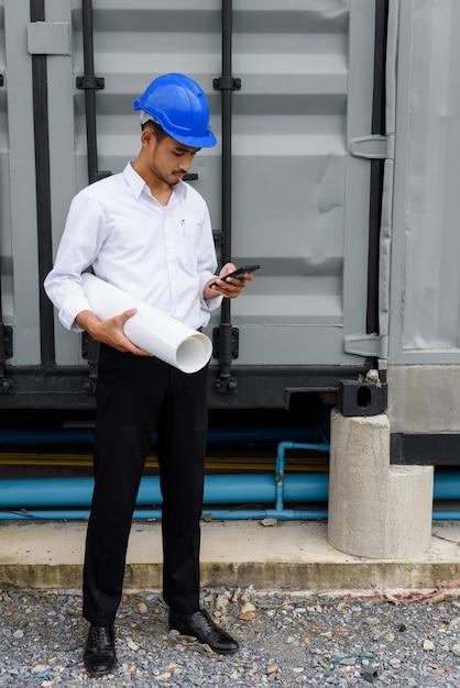Arabische ingenieurstekst op telefoon bij bouwwerf Premium Foto