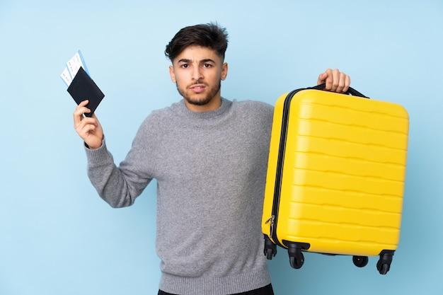 Arabische knappe man op blauwe muur ongelukkig in vakantie met koffer en paspoort Premium Foto