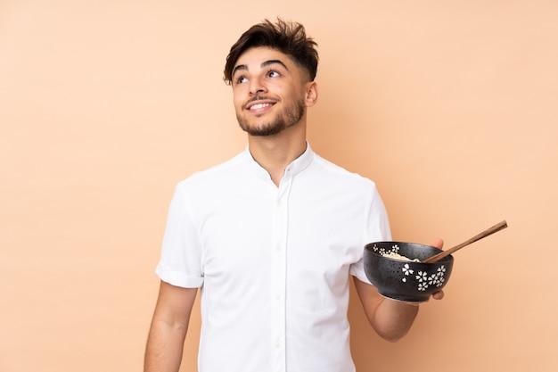Arabische knappe mens die op beige muur omhoog terwijl het glimlachen terwijl het houden van een kom noedels met eetstokjes kijkt Premium Foto