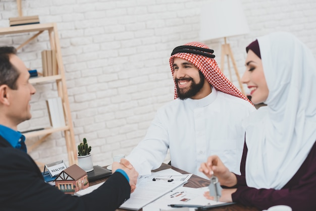 Arabische man en vrouw ontvangen sleutels van het nieuwe huis. Premium Foto