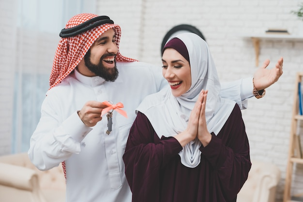 Arabische man geeft nieuw huis sleutels aan gelukkige vrouw. Premium Foto