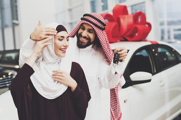 Arabische man koopt geschenkauto aan mooie dame in hijab. Premium Foto