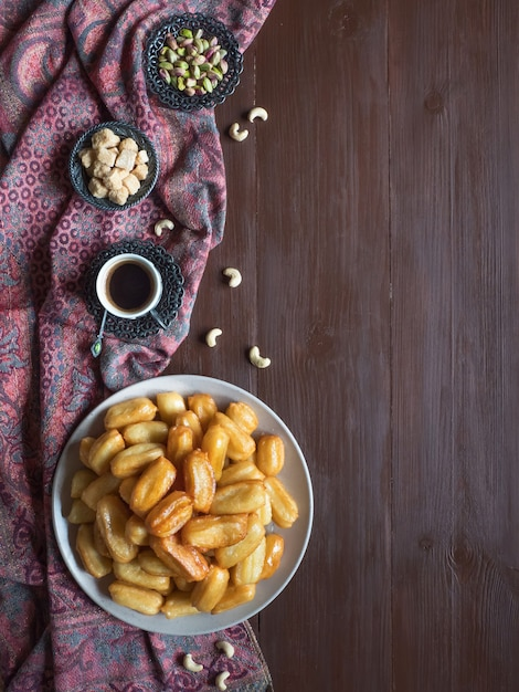 Arabische snoepviering eid ramadan. traditioneel turks dessert tulumba - tulumba tatlisi op houten achtergrond Premium Foto