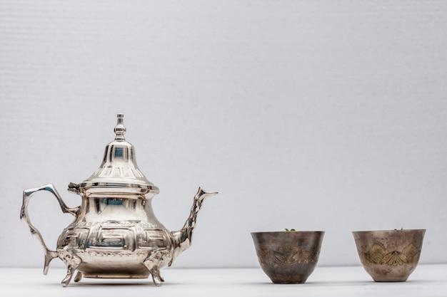 Arabische thee in koppen met theepot op witte lijst Gratis Foto