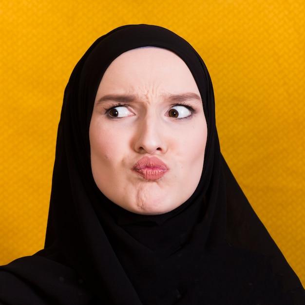 Arabische vrouw die verwarde gelaatsuitdrukking op zwarte achtergrond maakt Gratis Foto