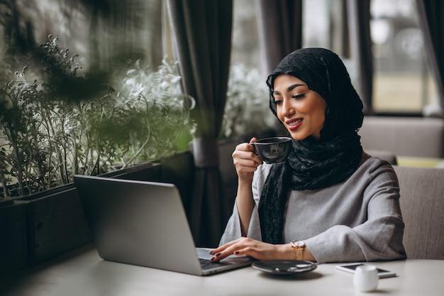 Arabische vrouw in hijab binnen een koffie die aan laptop werkt Gratis Foto