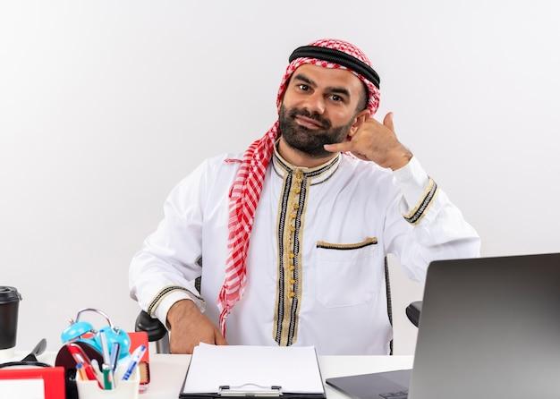 Arabische zakenman in traditionele slijtage zittend aan de tafel met laptop, bel me gebaar glimlachend werken in kantoor Gratis Foto
