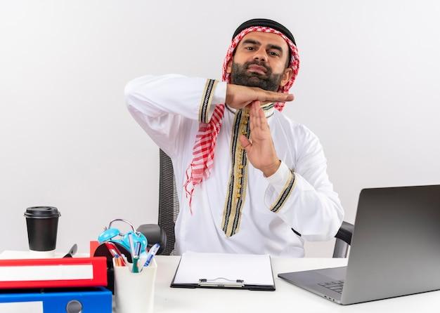Arabische zakenman in traditionele slijtage zittend aan de tafel met laptopcomputer time-out gebaar maken met handen werken in kantoor gehinderd Gratis Foto