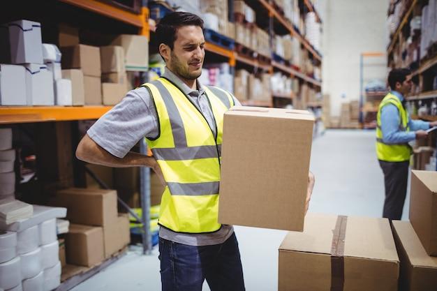 Arbeiders dragende doos in pakhuis met rugpijn Premium Foto