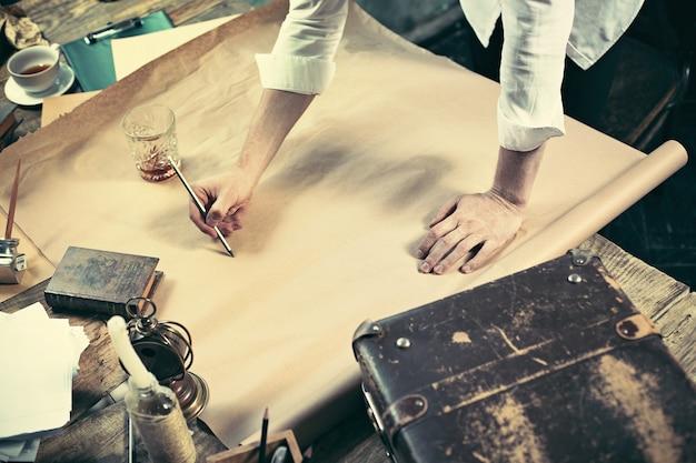 Architect die aan tekentafel in bureau werkt Gratis Foto