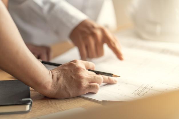 Architect en ingenieur werkt tekendocument over projectplanning en voortgang van het werkschema op de bouwplaats voor woningbouw Premium Foto