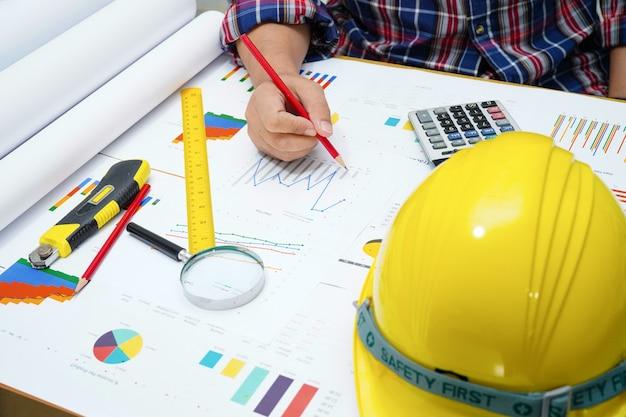 Architect of ingenieur werkend projectboekhouding met grafiek in bureau. Premium Foto