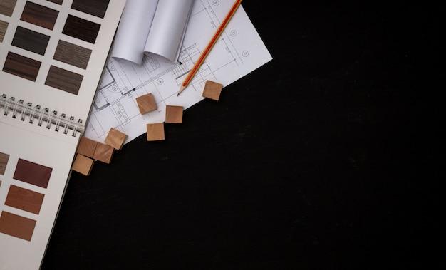 Architect ontwierp het gebouw in het ontwerpbureau, de plattegrond met catalogi decoratieve materialen en andere accessoires op de zwarte houten tafel. Premium Foto