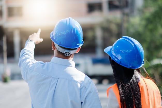 Architecten en ingenieur op een bouwplaats kijken naar blauwdrukken en wijzen. Premium Foto