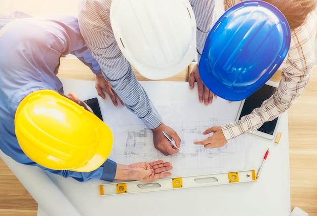 Architecten en ingenieurs komen bijeen en plannen gezamenlijke actie met commitment. afbeelding bovenaanzicht. Premium Foto