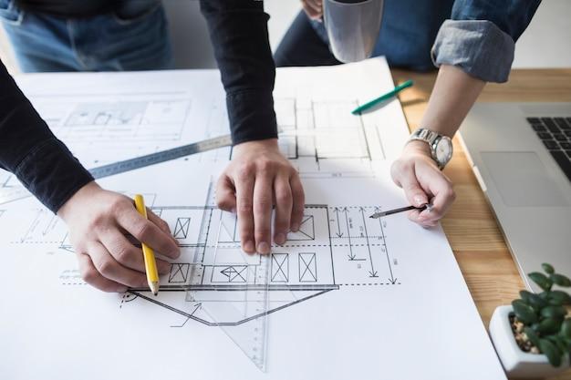 Architectenhanden die aan blauwdruk aan houten bureau op kantoor werken Gratis Foto