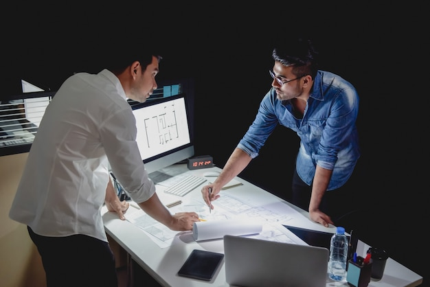 Architectenteam die project bespreken bij nacht Premium Foto