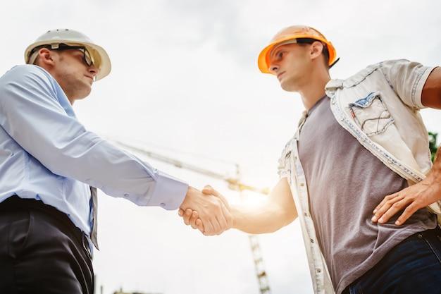 Architectingenieur het schudden overhandigt andere hand bij bouwwerf. zakelijk teamwork, samenwerking, succes samenwerkingsconcept Premium Foto