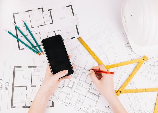 Architectuurconcept met de bouw van plan en smartphone Gratis Foto