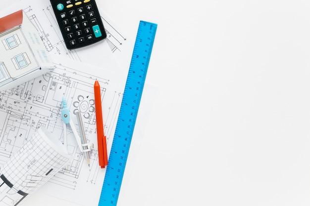 Architectuurlevering met calculator op wit bureau Gratis Foto