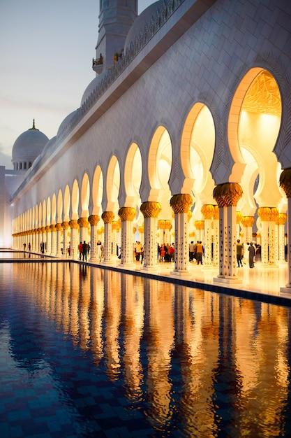 Archs of shekh zayed grote moskee weerspiegelen in het water daarvoor Gratis Foto