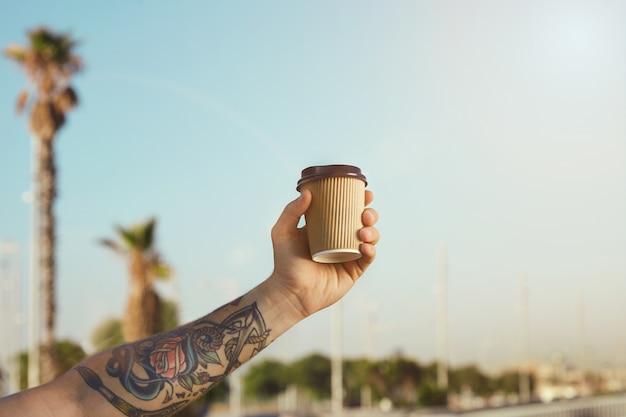 Arm en hand van een getatoeëerde man met een beige wegwerp koffiekopje van golfkarton tegen de helderblauwe lucht en palmbomen Gratis Foto