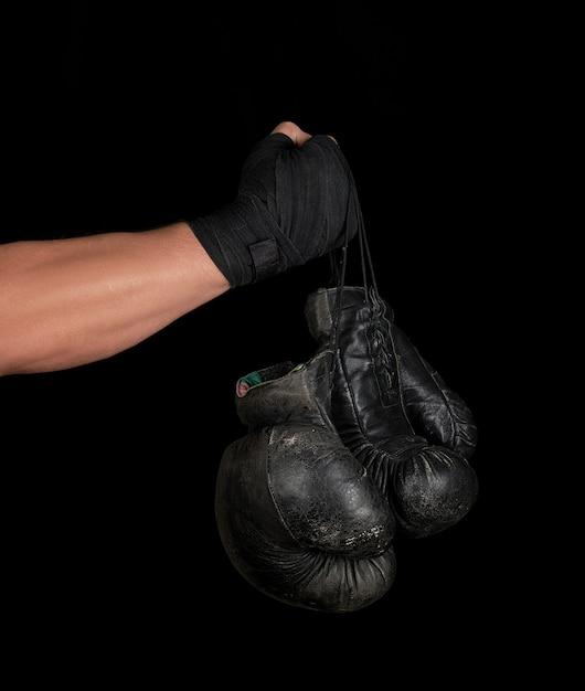 Arm gewikkeld in een zwart elastisch sportverband houdt een paar oude vintage lederen bokshandschoenen Premium Foto