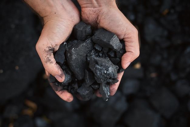 Arme man van middelbare leeftijd met de handen van steenkool te koop Premium Foto