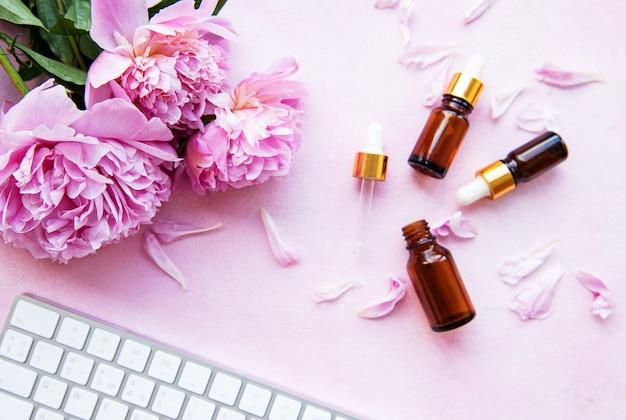 Aromatherapie essentiële oliën en roze pioenrozen Premium Foto