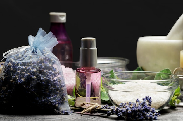 Aromatische compositie van lavendel, kruiden, cosmetica en zout op een donker tafelblad Premium Foto