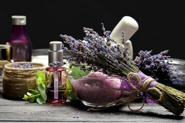 Aromatische samenstelling van lavendel, kruiden, cosmetica en zout op een donker tafelblad Premium Foto