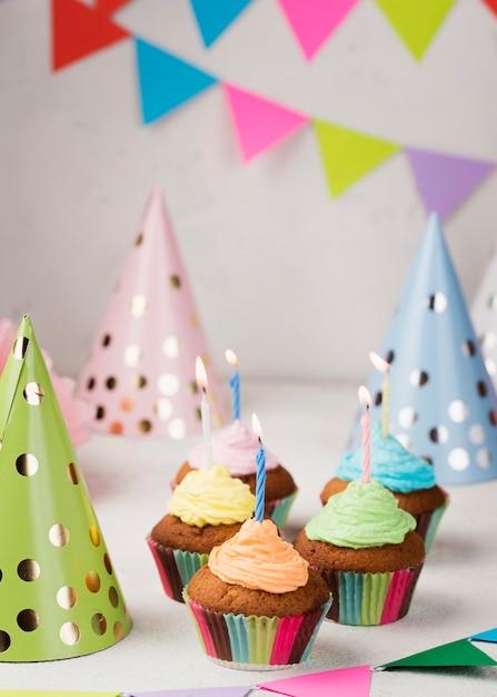 Arrangement met muffins, kaarsen en feestmutsen Gratis Foto