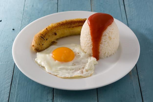 Arroz a la cubana typische cubaanse rijst met gebakken banaan en gebakken ei op een bord op houten tafel. Premium Foto