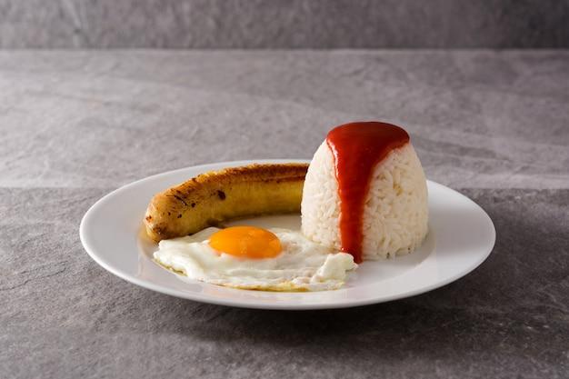Arroz a la cubana typische cubaanse rijst met gebakken banaan en gebakken ei Premium Foto