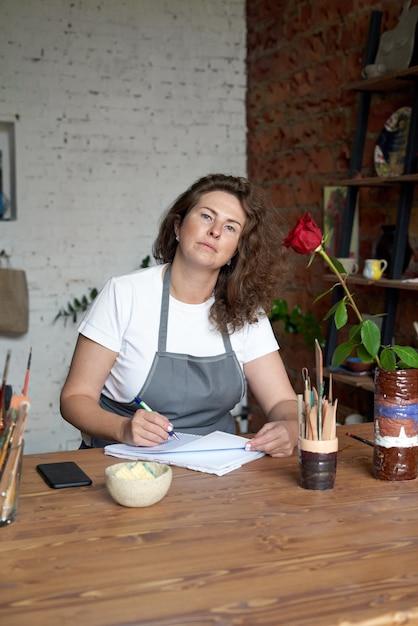 Artisanale vrouw die in notitieboekje schrijft en planning Premium Foto