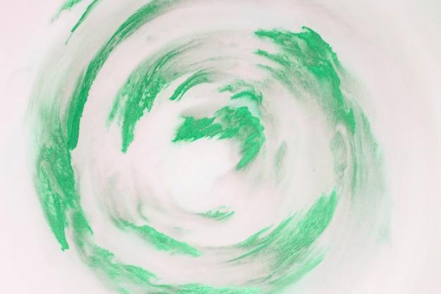Artistieke groene verfstreken in cirkelvorm op witte achtergrond Gratis Foto