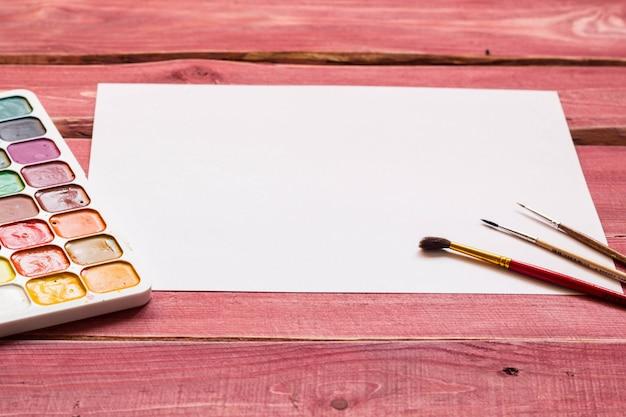 Artistieke mockup met leeg wit vel papier en art supplies rond inclusief aquarel Premium Foto
