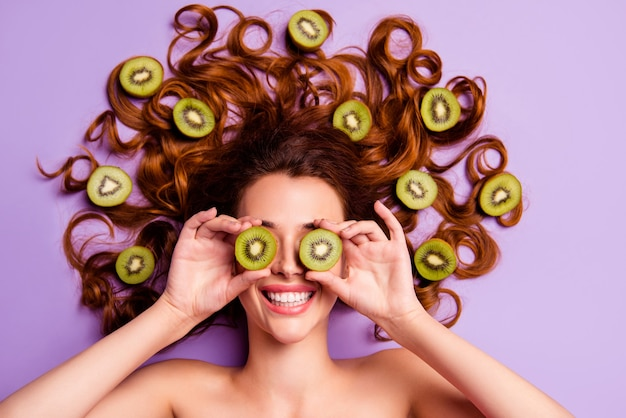 Artistieke roodharige vrouw poseren met kiwi in haar haar Premium Foto