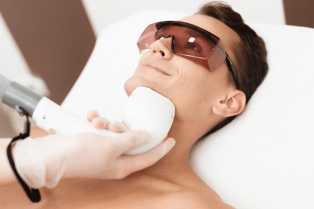 Arts behandelt zijn nek en gezicht met een speciaal apparaat Premium Foto
