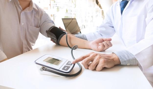 Arts controleren oude vrouw patiënten arteriële bloeddruk. gezondheidszorg Premium Foto