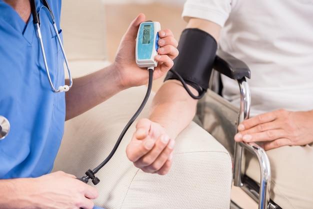 Arts die bloeddruk meet aan oudere patiënt. Premium Foto