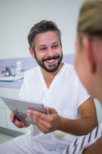 Arts die een digitale tablet houdt terwijl het spreken met patiënt Gratis Foto