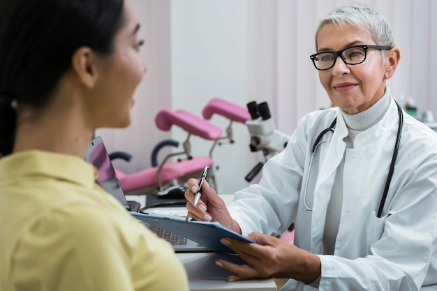 Arts die een patiënt in haar kantoor raadpleegt Gratis Foto